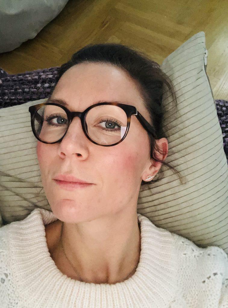 Deppig tjej med glasögon ligger på en kudde.